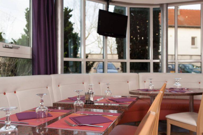 Confort et clarté dans la salle de restaurant du Géographotel Roissy.